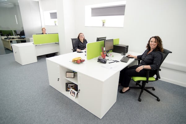 Copy Print Services 10 years old 3 staff sat at desks smiling