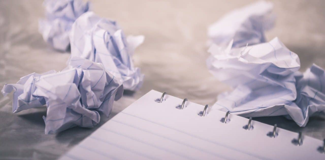 Crumpled up pieces of lined paper from a note pad